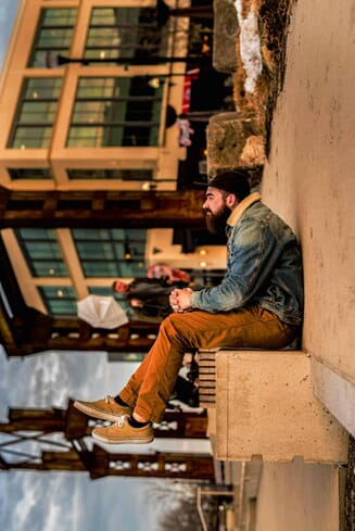 Forced perspective photography of a man sitting on the sidewalk