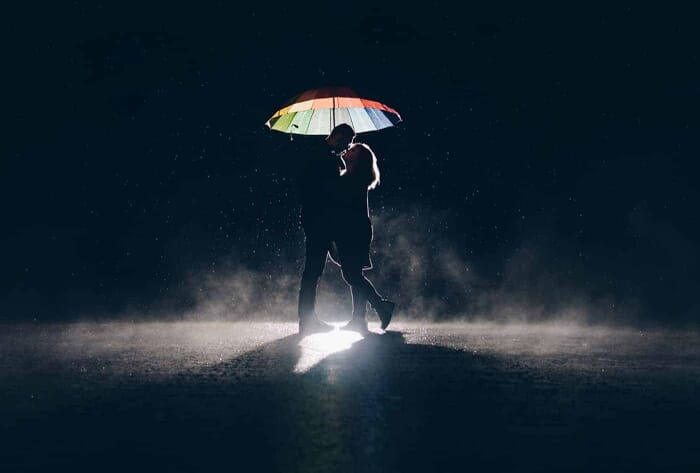 A silhouette of a couple under an umbrella in the rain at night.