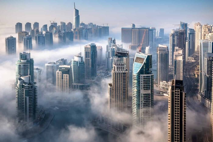 An impressive aerial top view of the Dubai Skyline on a foggy day.