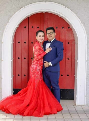 Full body picture of couple leaning to each other and facing the camera