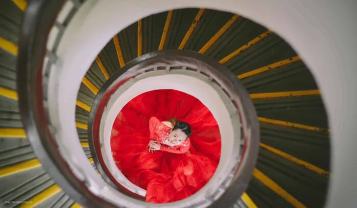 spiraling staircase with girl in gown in the middle