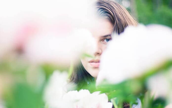 portrait with sharp eye showing through flowers
