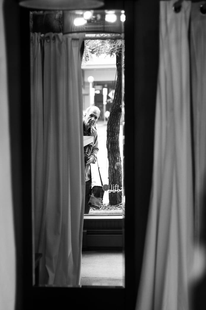 person peering through window street photography