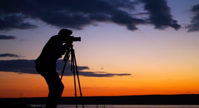 photographer with photography gear tripod setup